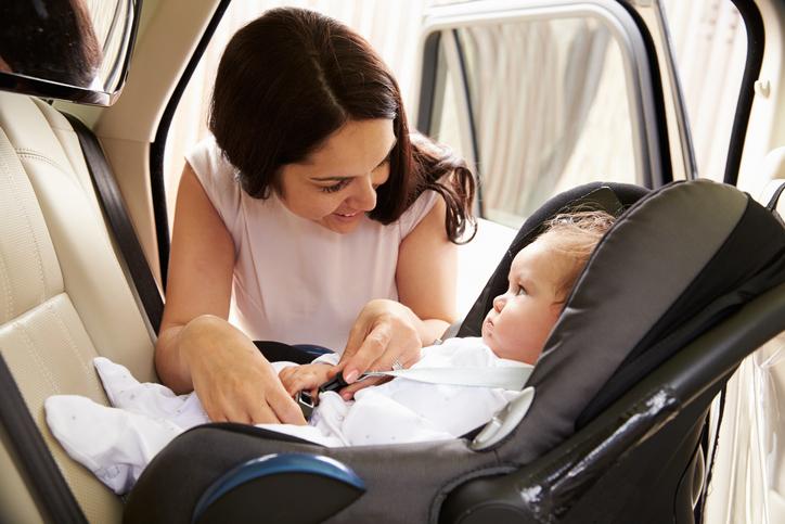 Mor sætter baby tilrette i autostol